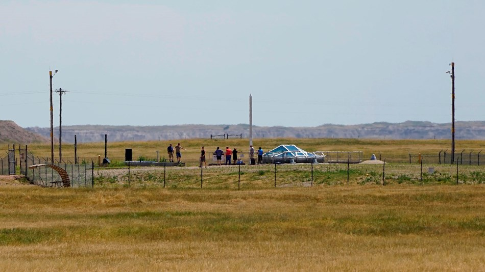 People stand inside a fenced compound on a prairie landscape