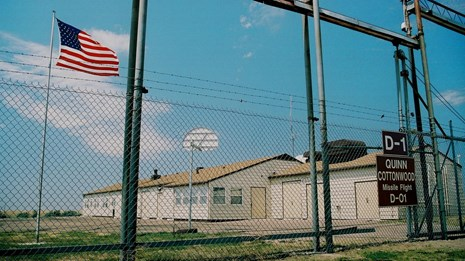 An American flag flys in front of a building inside a high fence