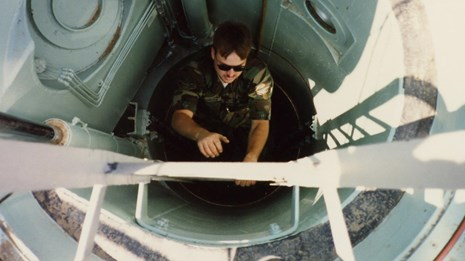 Airman climbing a ladder out of a cylindrical hatchway.