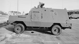 A heavy armored vehicle in a parking lot.