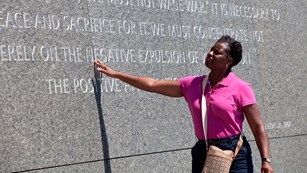 Visitor reading inscriptions within memorial