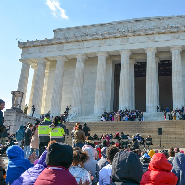 Crowd watching a school group behind a podium on the steps of the Lincoln Memorial
