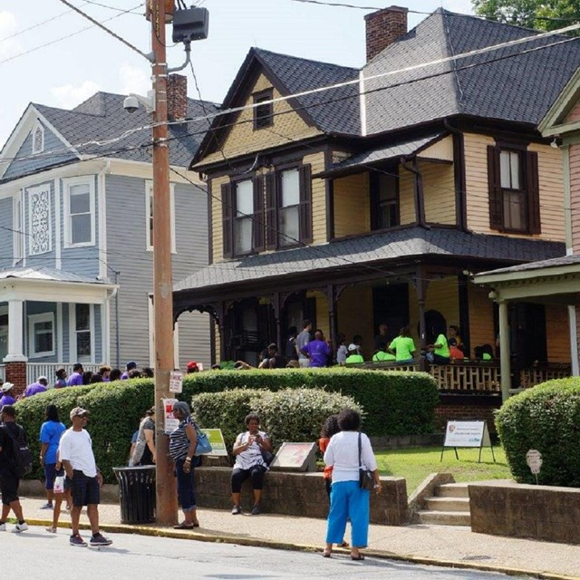 Visitors gathered outside of a two-story yellow house on a neighborhood street