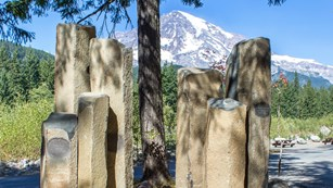 Two clusters of basalt columns stand in front of a view of Mount Rainier.
