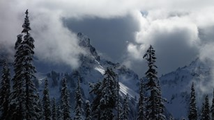 Clouds swirl around the snowy peaks of the Tatoosh Range.
