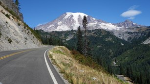 A road curves up the side of a valley towards Mount Rainier.