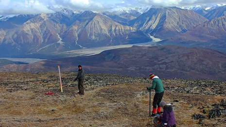Researchers install equipment on a mountain top.