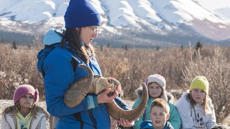 instructor holds dall sheep horns as children sit and listen