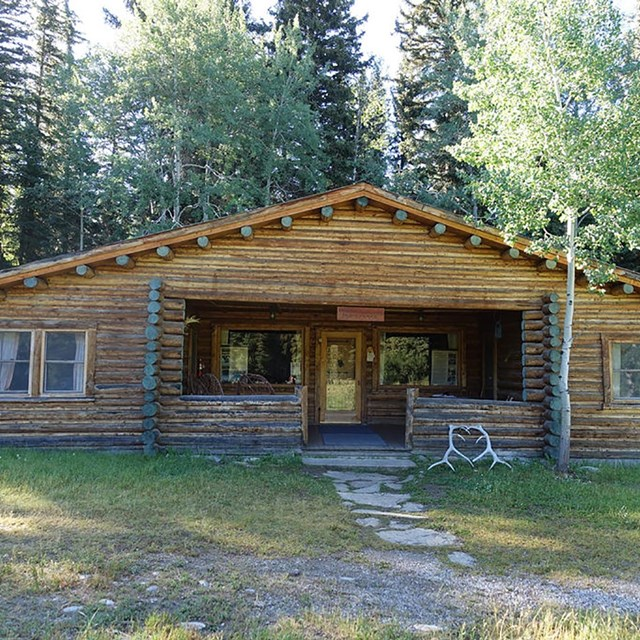 a log cabin with forest behind it