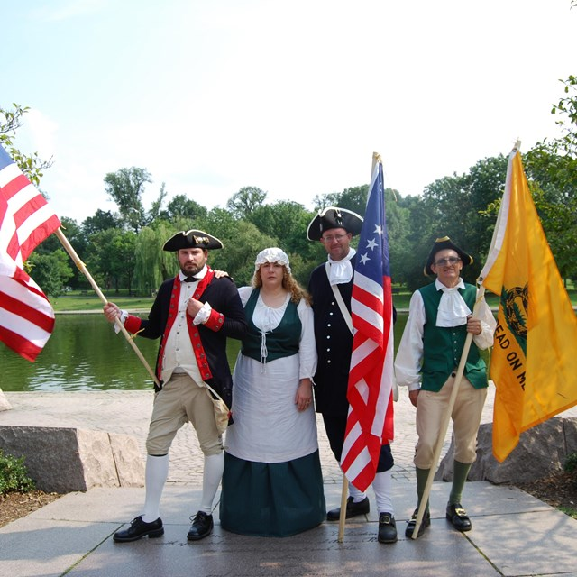 Revolutionary War Era reenactors holding period flags