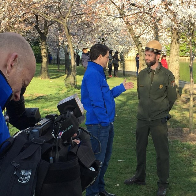 Ranger talking to a reporter in front of a camera