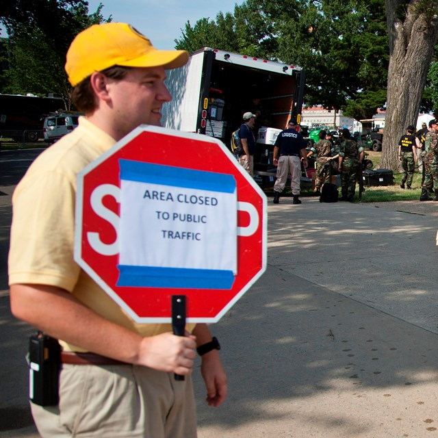 A volunteer showing visitors that the area is closed with a sign.