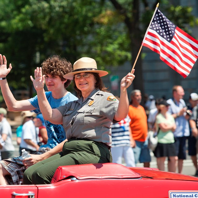 A Park Ranger waves an American Flag from a parade car in the Independence Day Parade.