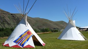 One painted and one non-painted tipi set up on fresh grass with hills and blue sky in background.