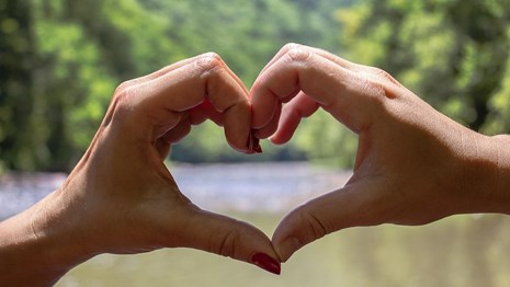 Two hands form a heart over the river