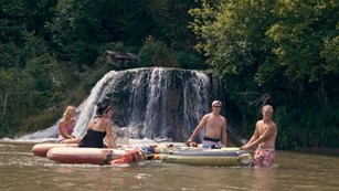In a still shot from a video, four people float on tubes in front of a waterfall on the Niobrara.