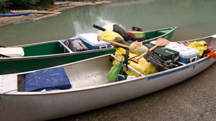 Canoes loaded for camping  prepare to launch at the lakes edge.
