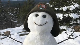 Snowman wearing a ranger winter hat
