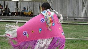 Native shawl dancer wearing a pink shawl