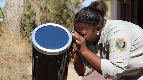 Female volunteer looking through telescope