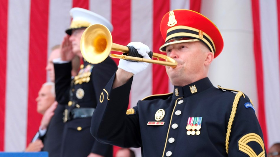 Military bugler playing in front of a large US flag