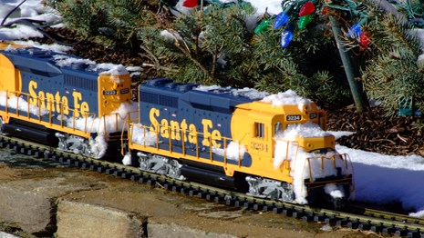 Toy train covered in snow next to evergreen branches with holiday lights