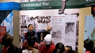 Ranger talking to school group in an exhibit about kids during World War II