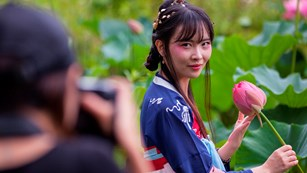 Photographer taking a picture of a woman in traditional Japanese attire holding a flower