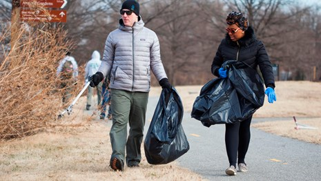 Two people carrying garbage bags in a park
