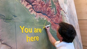 Person installing a wall map of the Grand Canyon