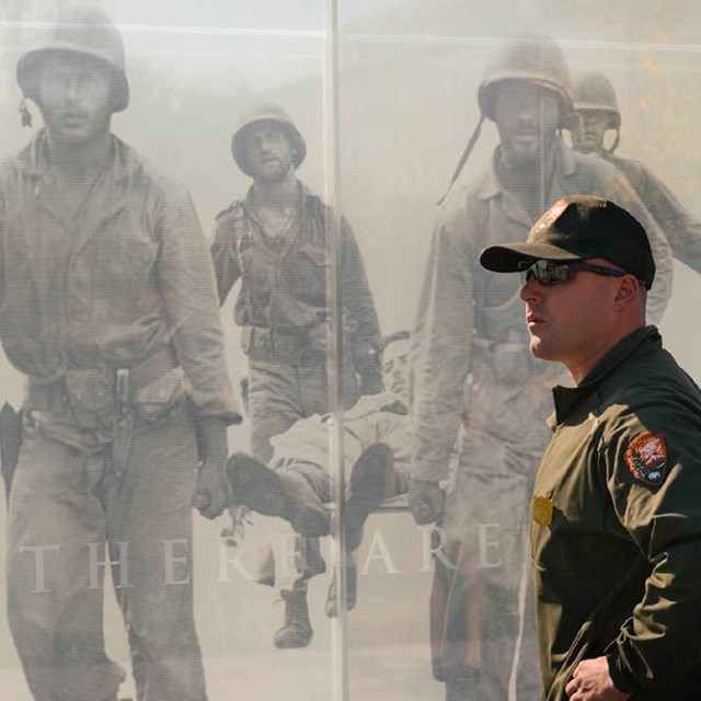 Ranger standing in front of a memorial wall with images of soliders