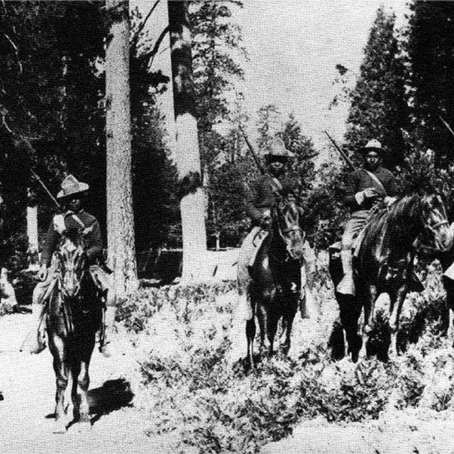 Historic black and white photograph of mounted Buffalo Soldiers at Yosemite
