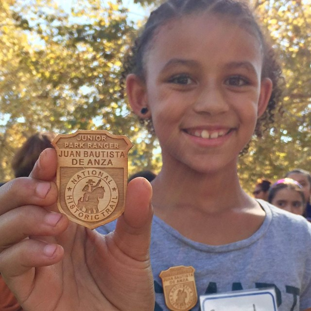 Kid holding a Junior Ranger badge