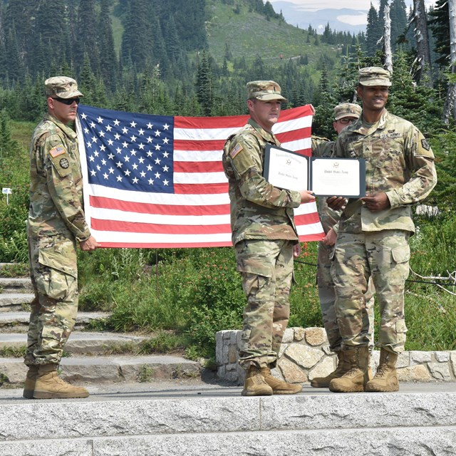 Soldiers holding a US flag and certificate