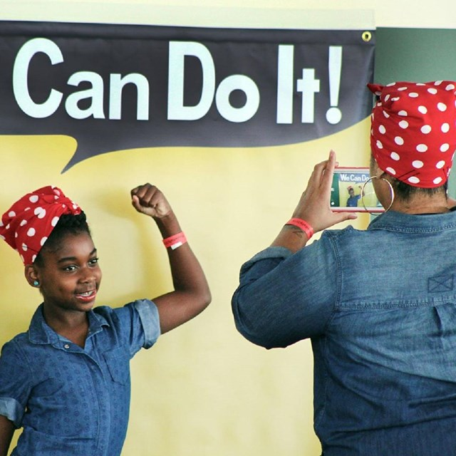 Woman taking a picture of girl posing as Rosie the Riveter while they are both dressed as Rosies