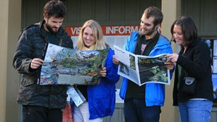 Visitors look at a newspaper in front of a visitor center