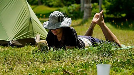 a woman reads a book on the grass outside her tent