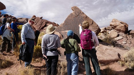A volunteer interpreter leads a group along a pale ridge in the Painted Desert