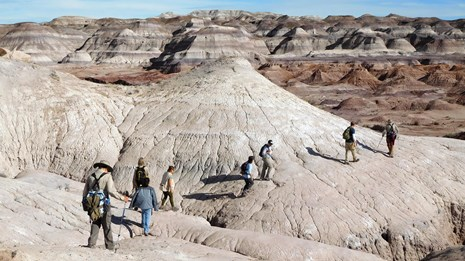 Hikers explore the route to Red Basin through colorful badlands