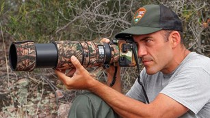 Candid of biologist in National Park Service hat aiming a camera lens.