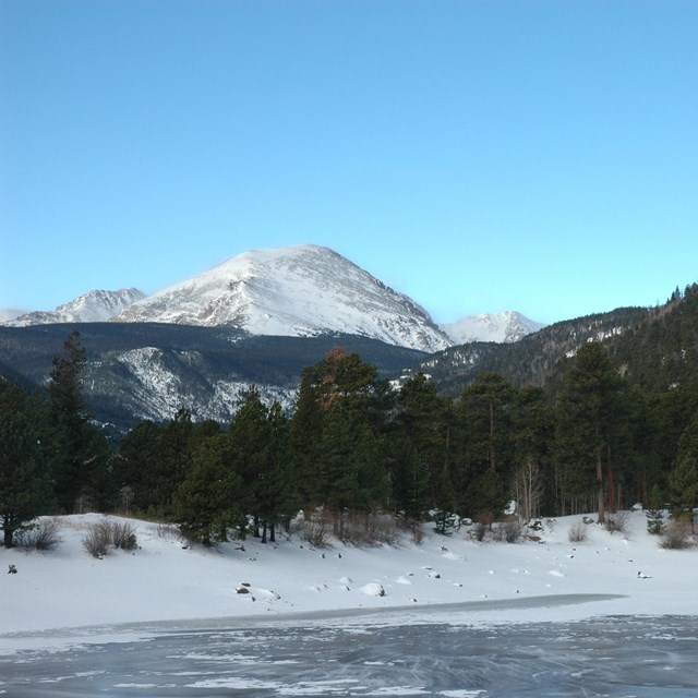 Mountain beyond a forest and frozen lake