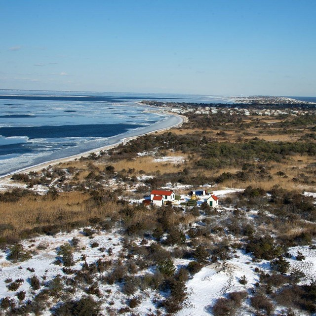 Aerial view of a barrier island beach with a dusting of snow