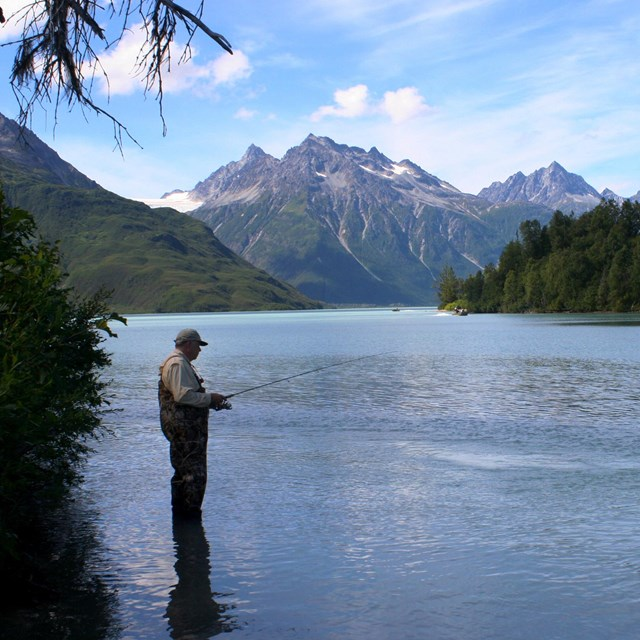 Fisher in waders standing in water holding fishing pole with peaks in background