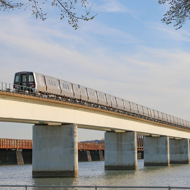 Metro train going across bridge with river flowing underneath