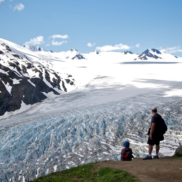 Hikers overlooking large mountain glacier