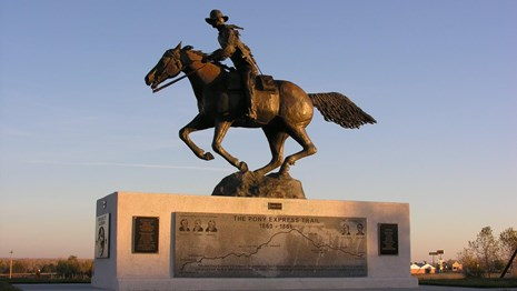 A large metal statue of a man riding a horse.