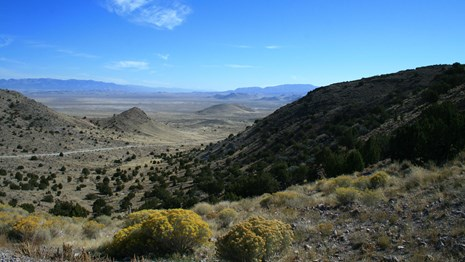 A desert canyon leading out onto a vast desert landscape.
