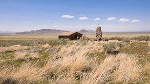 Tall grass leads to a distant barn set in an expansive grassland with distant mountains.