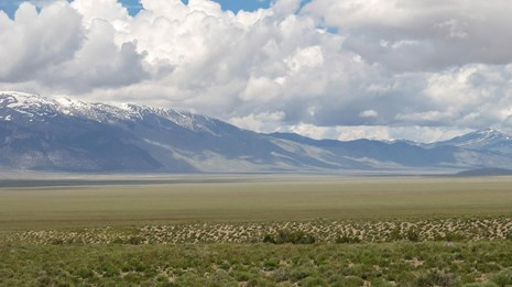 A vast grassy range leads to towering, snow-capped distant mountains, under a cloud filled sky.