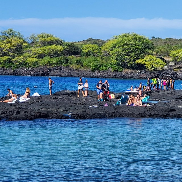 People gather on black lava rock at the popular snorkel spot,